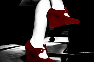 wearing red shoes sitting at desk. head over heels