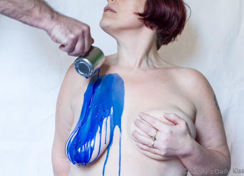 Molly with blue wax being poured on her breast