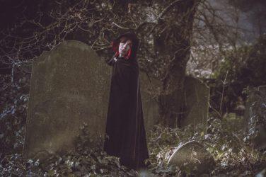 Molly in hooded cloak in gravestones