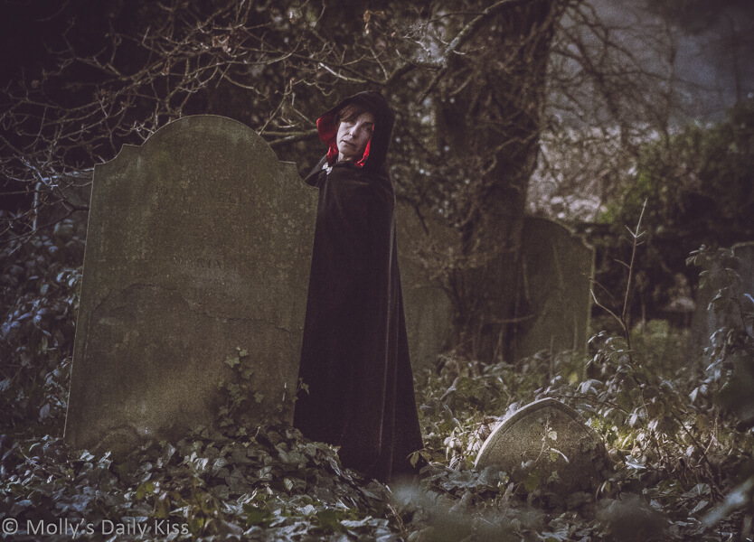 Molly in hooded cloak in gravestones