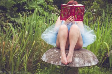 Molly in blue tutu sitting on stone toadstool reading fairy tale book. fairy Folk