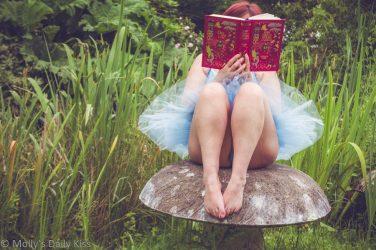 Molly in blue tutu sitting on stone toadstool reading fairy tale book. fairy Folk