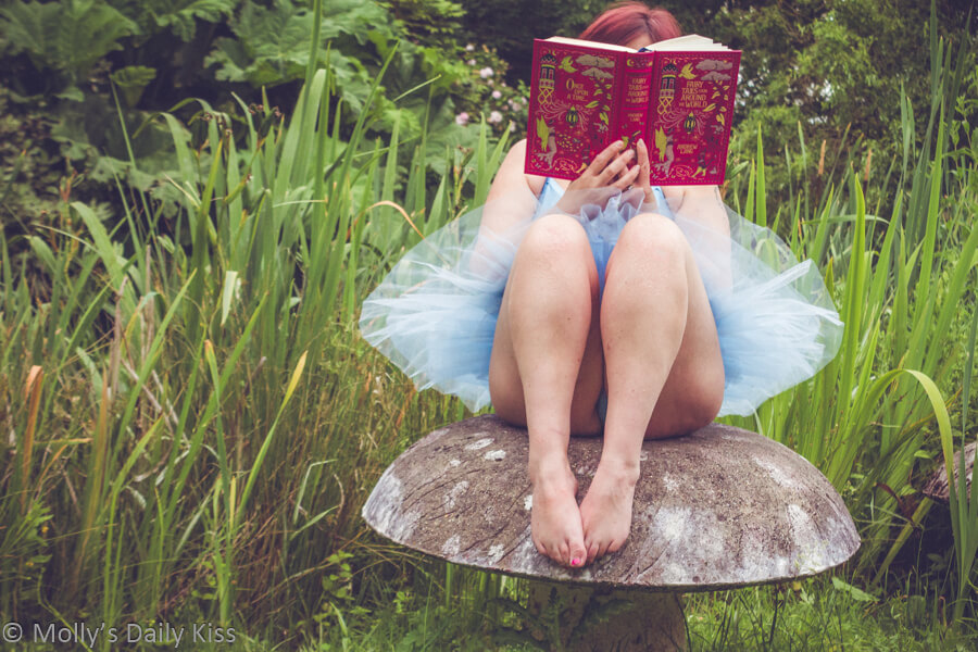 Molly in blue tutu sitting on stone toadstool reading fairy tale book