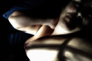 Molly laying in sunlight and shadows topless with flushed cheeks