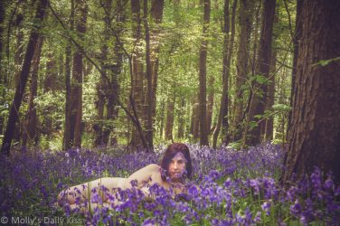 Molly laying naked in the bluebells looking directly at the camera. Fleeting in display