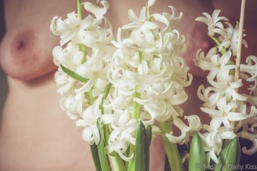 Mollys boobs out of focus behind white hyacinths