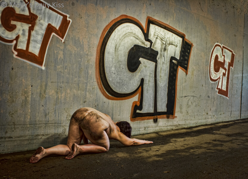Molly crawling naked through the dirt in a subway with the letter GT in graffiti on the wall