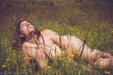 MOlly laying in field of buttercups looking up at the sun