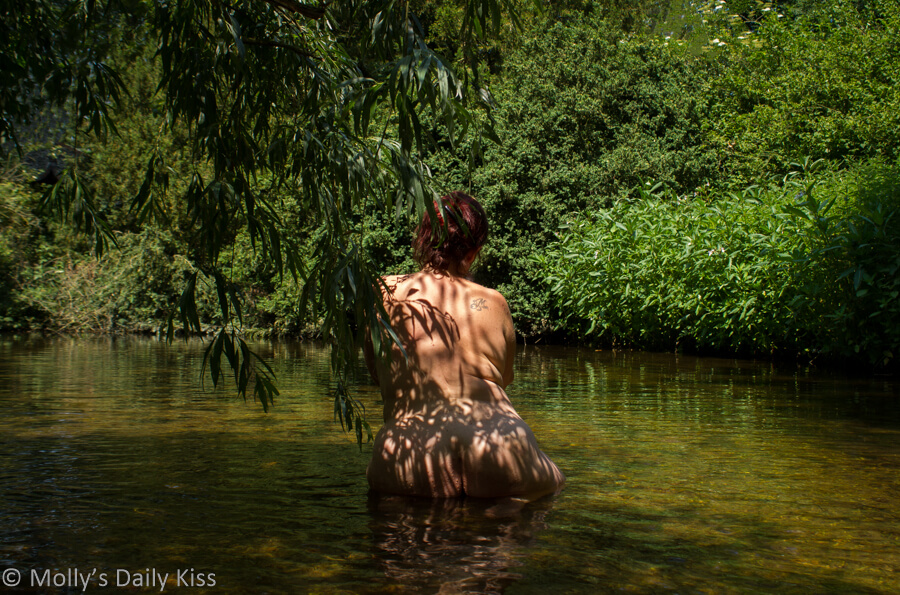 molly kneeling in the stream under weeping willow with shadow of leavs on her back