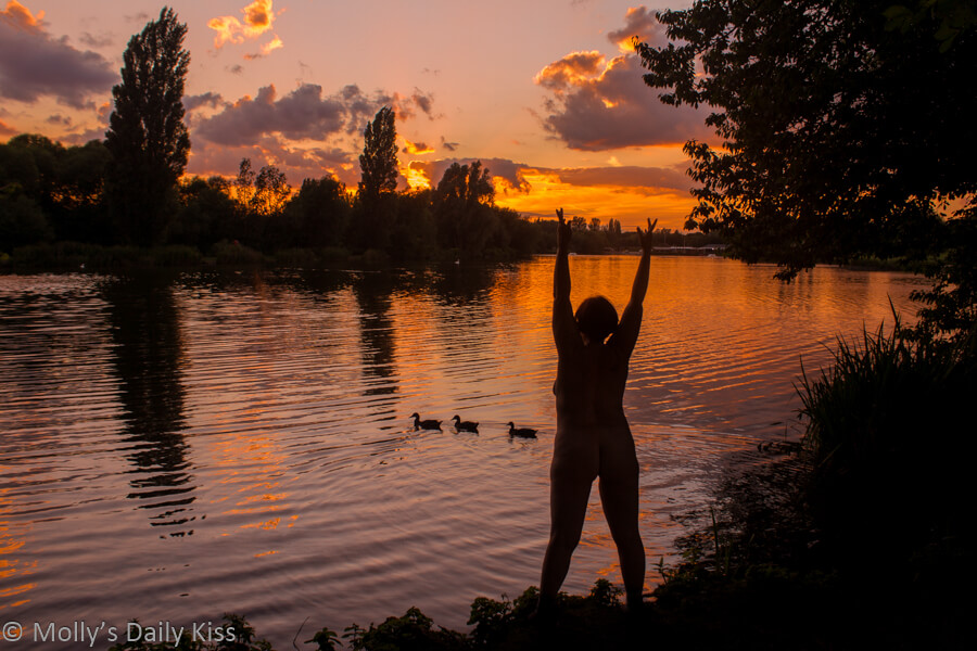 Molly naked on edge of lake with fiery gold sunset in the distance and three little ducks in a row on the water in front of her