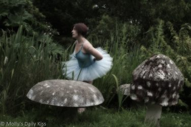 Molly in blue tutu with giant mushroom sculptures