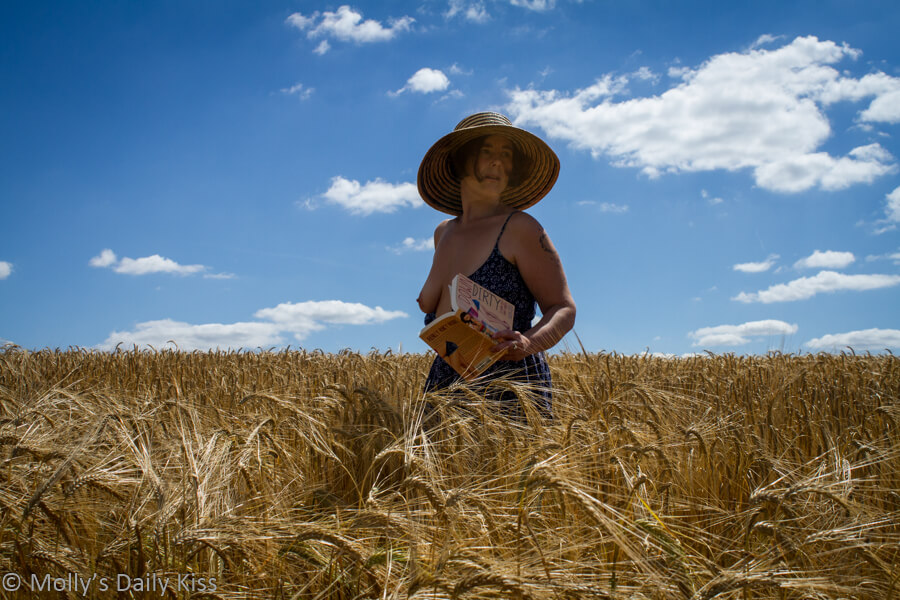 MOlly standing in field of golden wheat holding book with dress pulled down and breast exposed