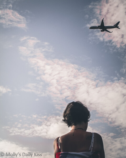 Molly looking up into the sky at a plane taking off