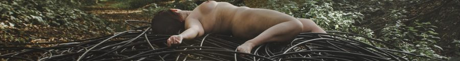 molly naked laying on abandoned cable in the woods