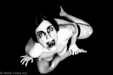 Molly topless looking up at the camera with silent scream wearing torn fishnets