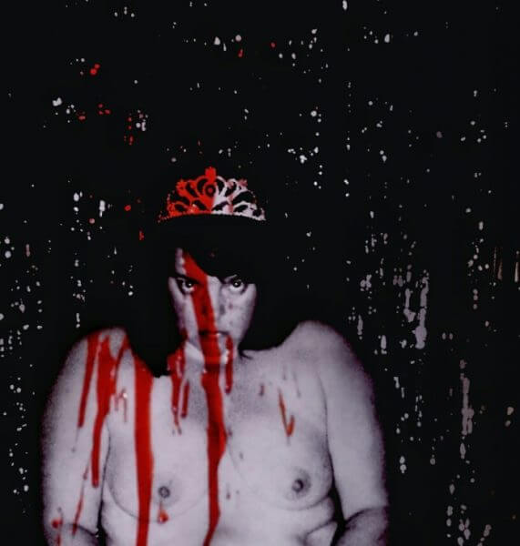 Phot b Maria Opens up of her topless wearing a crown covered in fake blood staring into the camera