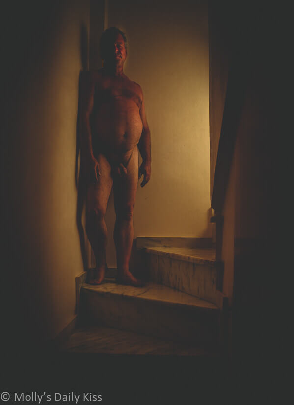 Michael standing naked in stair well with light shining on one side of his body