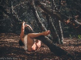 Molly hanging underneath tree in autumn woods with sunlight shining on her pussy for post called Autumn's Fire