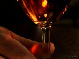 man holding stem of glass of rose wine