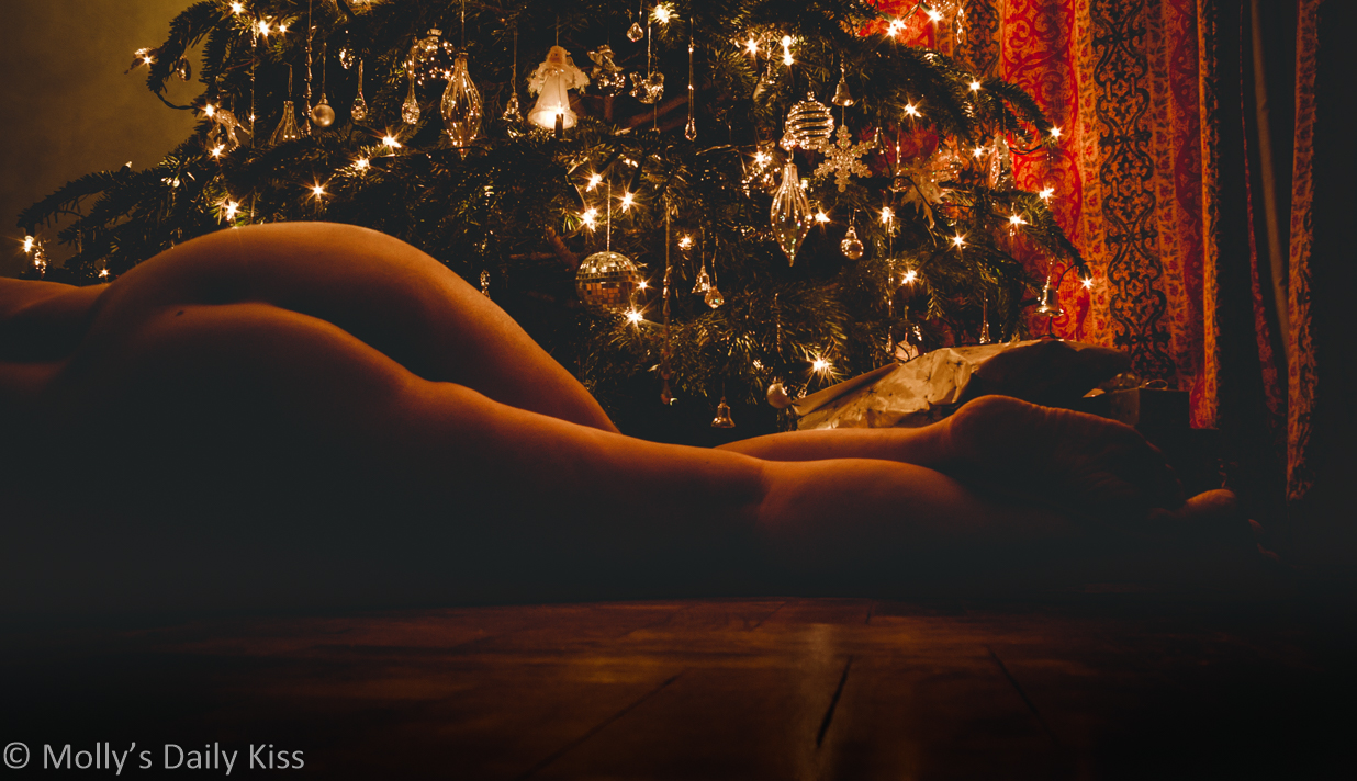 Molly laying on teh floor naked underneath Christmas tree