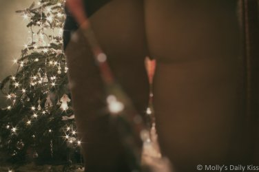 Mollys bottom in front of christmas tree with heart shaped gap between her thighs for a post called Maybe Christmas