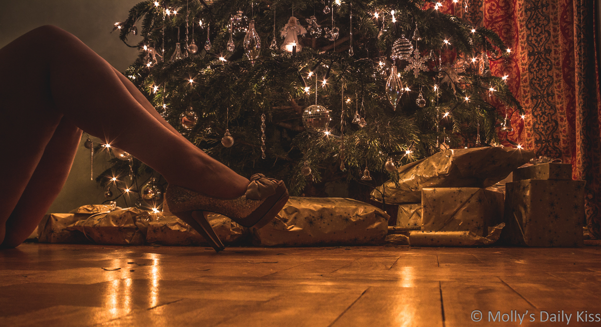 Mollys legs in silver glitter high heels in front of Christmas tree and presents on Christmas Eve