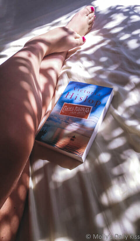 Molly's legs in dappled sunlight with book on the bed