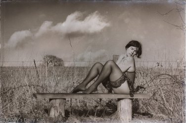 molly sitting on bench in winter landscape iwht clouds in the sky above her edited to look like a wetplate image