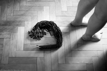 Flogger with metal beads on the end curled on the floor behind Molly's legs who is standing in the corner of the image