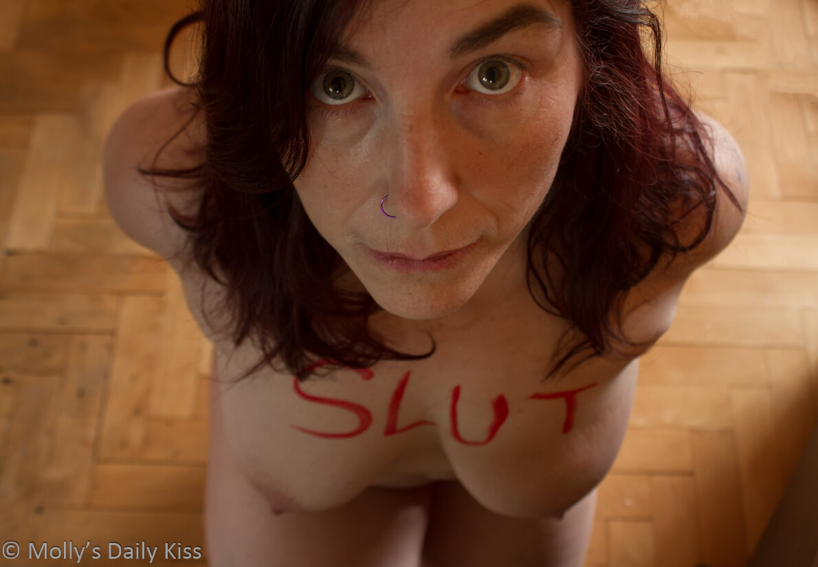 Molly kneeling naked with the word slut written across her chest