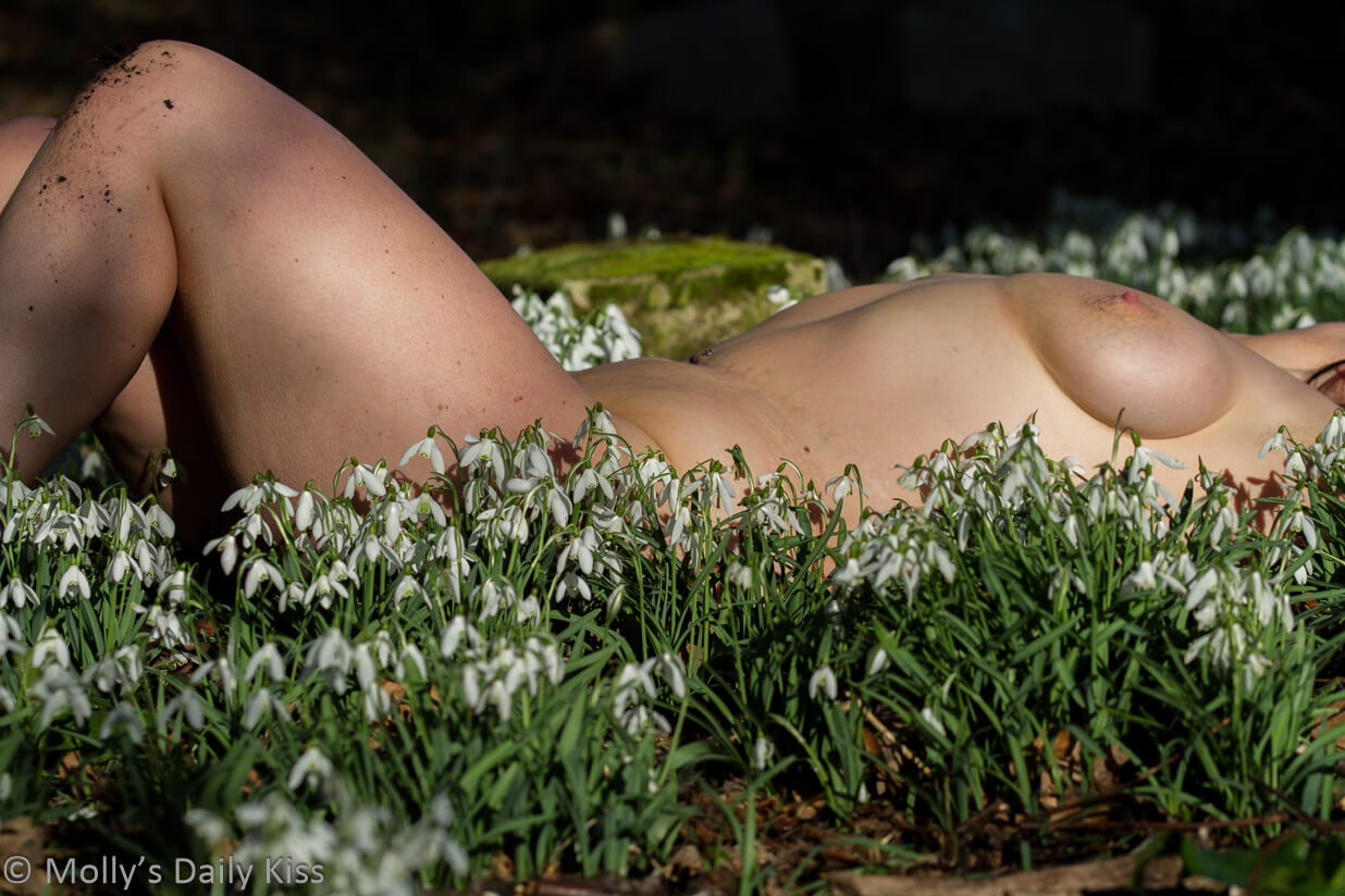 molly laying on her back naked in the snowdrops