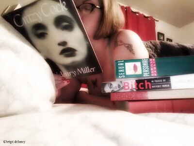 Woman laying on bed reading sexy books