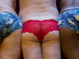 3 bottoms in a row. 2 woman in mens pants with man in red lace panties in the middle