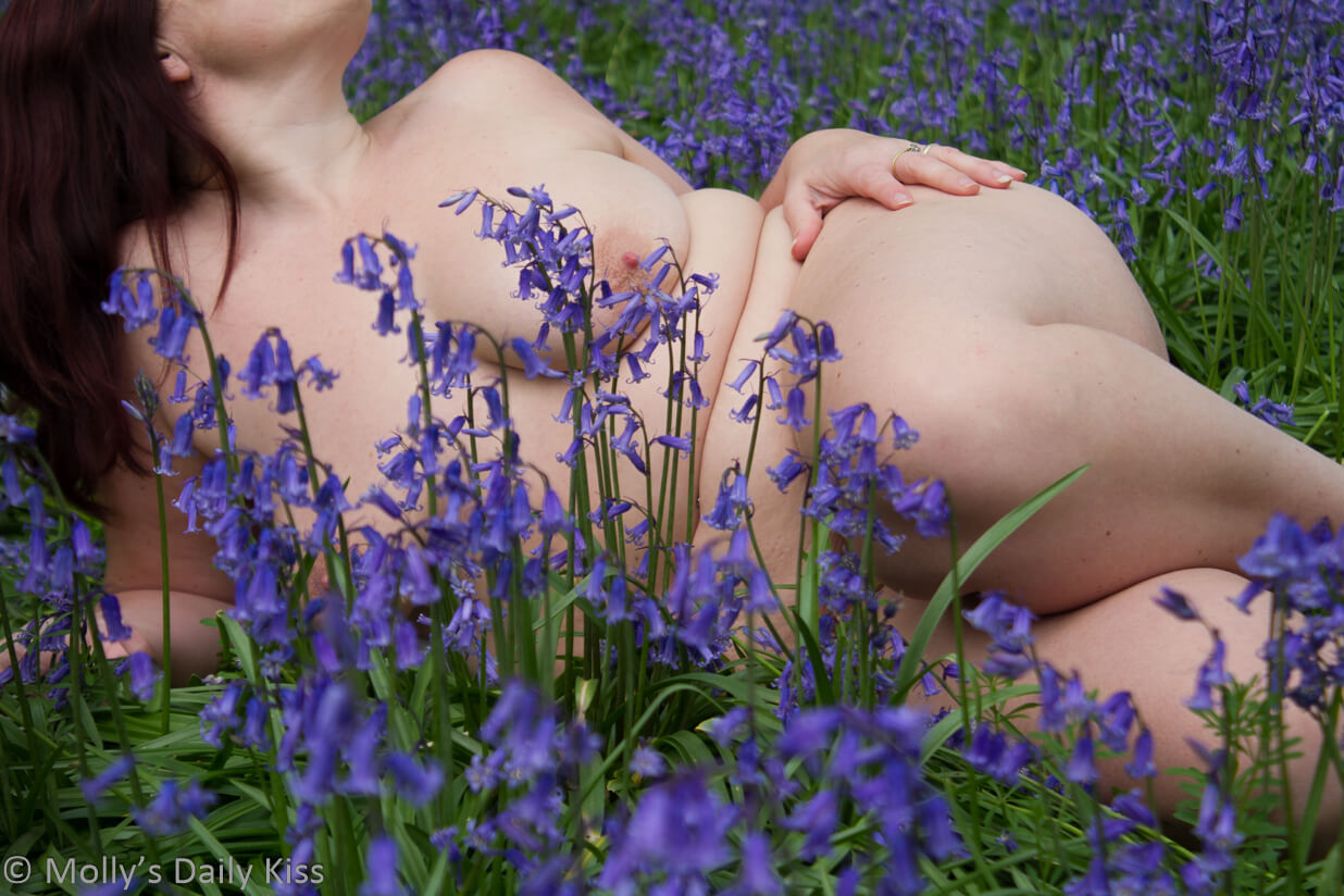 Molly laying on her side naked in the bluebells