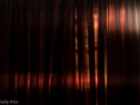 red curtains with sunlight shining round the edge