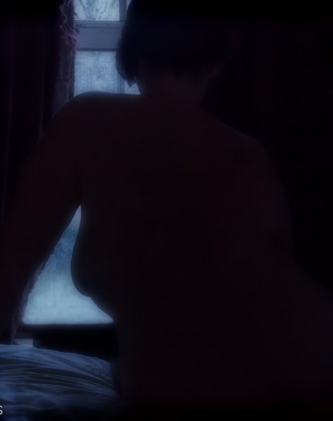 Molly sitting on edge of bed in dark room with light from curtain showing round her naked form