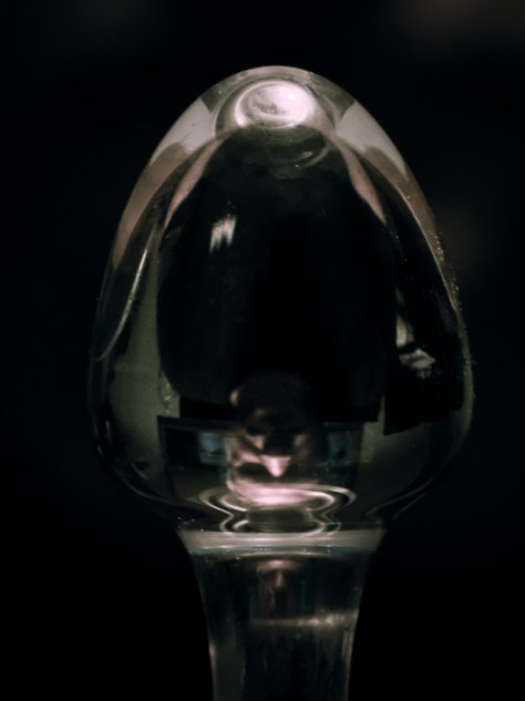 Man's face reflected in the bulb head of a glass dildo for a post called Take a Seat