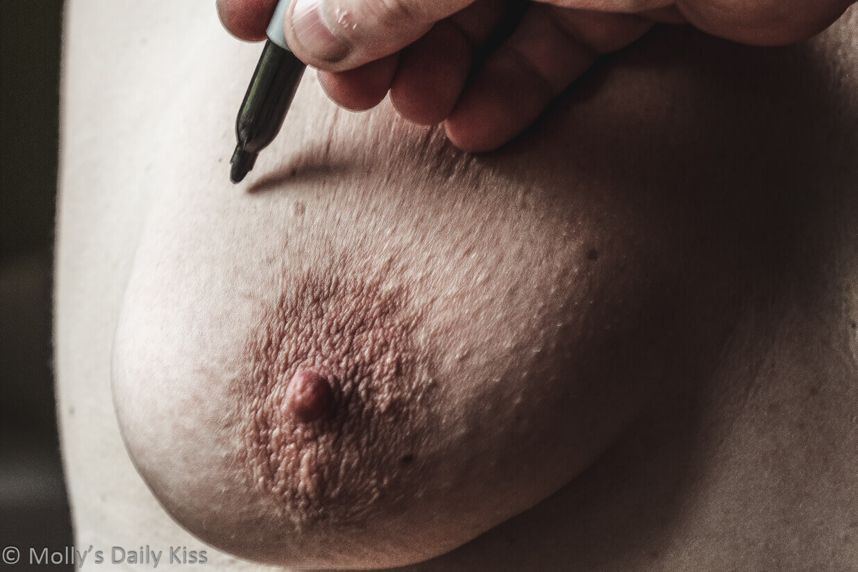 Hand holding black pen about to write on molly's breast