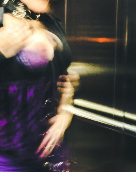 Blured image of Molly in a lift with one breast out looking into the mirrored wall for blog post called crescendo
