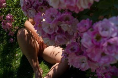 Molly languishing naked beneath pink roses with her legs spread toughing her cunt