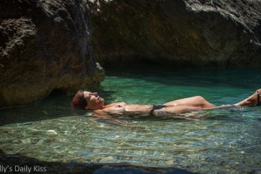Molly floating topless in blue green Greece sea