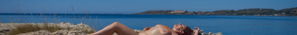 Molly laying naked on rock for Robes of Glorys jutting out into the sea