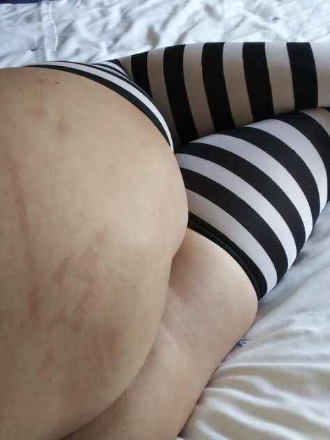 Molly in black and white striped stocikngs with black cane and red cane stripes on her bottom