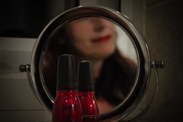 Bottle of red nail polish in front of small round mirror with molly relfected in the mirror wearing bright whore red lipstick