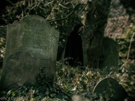 Molly dressed in black cape in background of old abandoned graveyard looking like a witch
