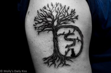 Tattoo on bicep of tree with a D shape trunk with a small s in the centre and a little black cat sitting on the branch