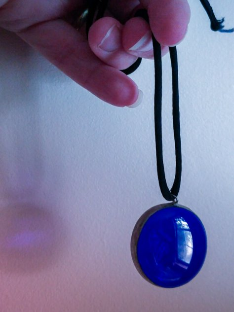 blue lass pendant held up against a wall for a post called spellbound
