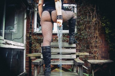 molly standing on wooden bench wearing black boots, fishnet tights and black thong holding chain looking femdom