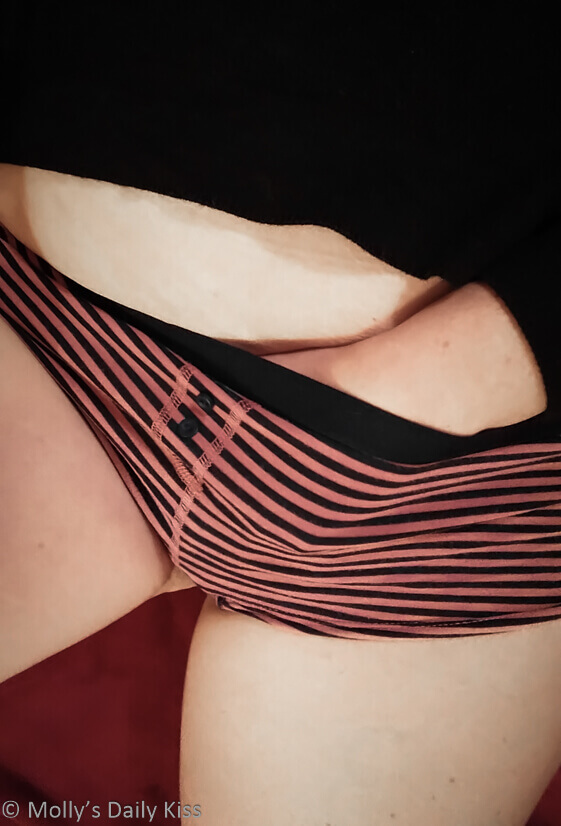 Molly with her hand disappearing into her striped knickers