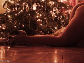 Molly wearing high heels crawling in front of Christmas tree